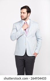 handsome elegant man with beard dressed in light-colored suit with attitude, isolated