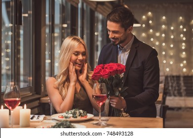 Handsome elegant man is giving roses to his beautiful girlfriend while making a surprise in restaurant, both are smiling