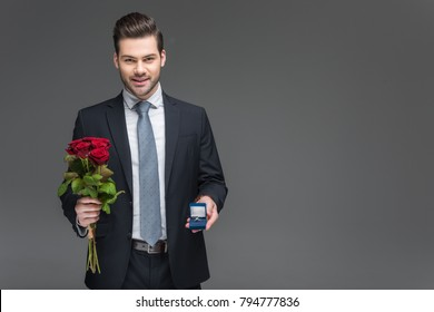 handsome elegant man holding bouquet of red roses and proposal ring, isolated on grey