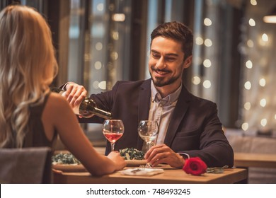 Handsome elegant man is pouring wine and smiling while having a date with his girlfriend in restaurant
