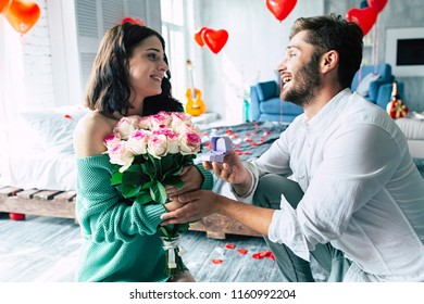 Handsome elegant man is proposing to his beautiful girlfriend, giving her roses and smiling while they having a romantic date at home
