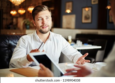 Handsome elegant man sitting at table in restaurant and talking to anonymous business partner with tablet