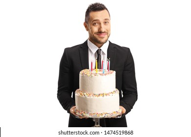 Handsome elegant man in a suit holding a cake with candles isolated on white background