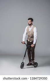 handsome elegant man in trendy waistcoat riding modern scooter on grey
