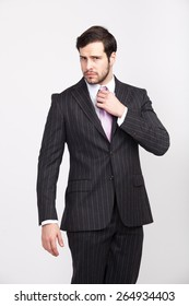 handsome elegant masculine man with beard, dressed in striped suit posing with attitude, isolated