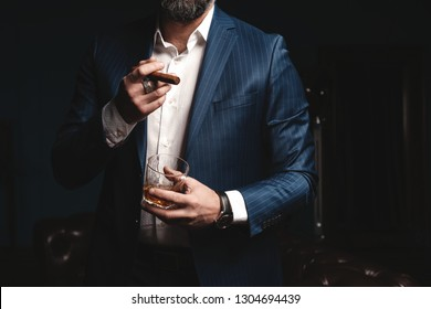 Handsome elegant mature man with cigar and a glass whiskey in a dark room