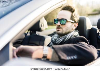 Handsome elegant serious man drives a cabriolet car