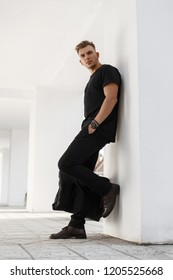 Handsome elegant young fashionable man in black stylish clothes with shoes and black bag posing near the white wall