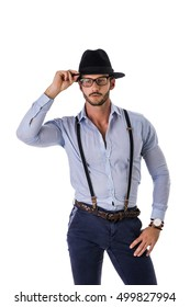 Handsome elegant young man with elegant shirt, suspenders and hat, isolated on white, smiling and looking at camera