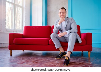 Handsome and elegant young man sitting on the red couch.