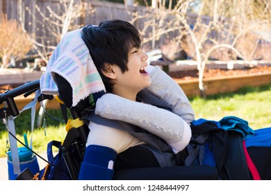 Handsome eleven year old disabled biracial boy in wheelchair sitting outdoors on a summer day, smiling