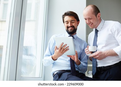 Handsome employee with touchpad explaining data to his colleague
