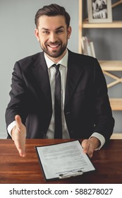 Handsome employer is holding an employment agreement, offering his hand and smiling while sitting at the table in his office