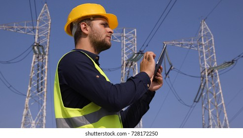 Handsome Engineer Man Using a Digital Tablet Looking Up on Electricity Pylon