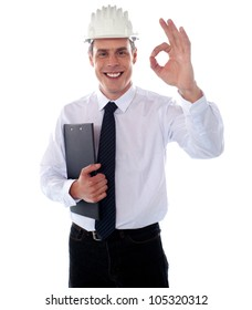 Handsome engineer showing okay gesture wearing safety helmet and holding clipboard
