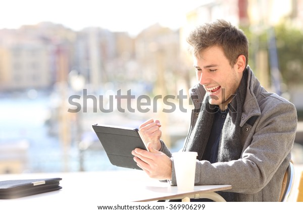 Handsome euphoric winner winning and watching a tablet in a coffee shop terrace of a port of urbanization with the sea in the background