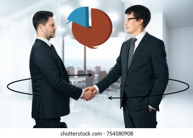 Handsome european businessman shaking hands in blurry office interior with business pie chart and arrows. Communication and teamwork concept