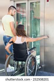 Handsome european man helping handicapped girlfriend at outdoor elevator
