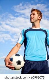 Handsome European man holding a football outdoors