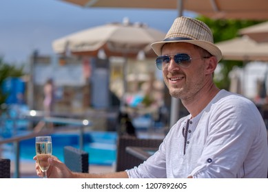 Handsome European man in sunhat and sunglasses is sitting in the pool bar and enjoying his vacations. He is holding the glass of champagne and smiling to the camera.