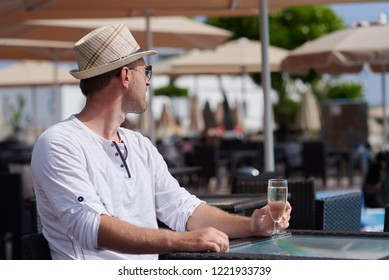 Handsome European man in sunhat and sunglasses is sitting in the pool bar and enjoying his vacations. He is holding the glass of champagne.