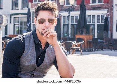 Handsome European young man. Wearing black shirt, vest and sunglasses. Attractive guy with beard, thinking. City and sunny background.