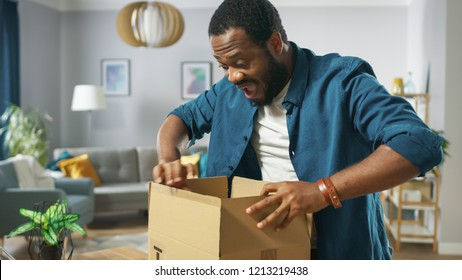 Handsome Excited Man Opens Cardboard Box Postal Package and Is Very Excited and Happy with Content. Man Package Unboxing.