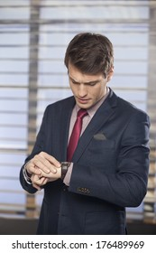 Handsome executive checking the time on his wrist watch