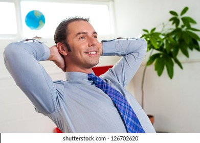 Handsome executive relaxing with hands at the back of his head, business concept.