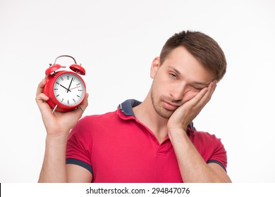 Handsome exhausted young man posing with red alarm clock. Blond man in pink T-shirt touching his cheek with left hand.
