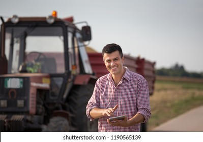 Handsome farmer with tablet standing in front of tractor with trailers in field