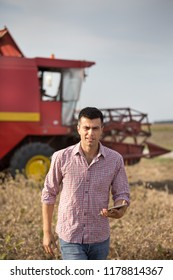 Handsome farmer with tablet standing in soybean field during harvest