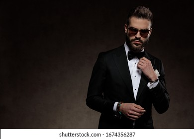 Handsome fashion groom adjusting his collar while wearing sunglasses and suit, standing on a wallpaper studio background