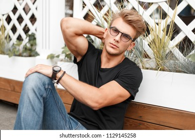 Handsome fashion man with a hairstyle with sunglasses in a black T-shirt with jeans is sitting on the beach
