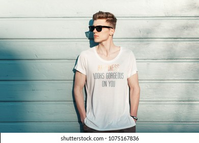Handsome fashion man hipster in stylish sunglasses in a white T-shirt posing near a blue wooden wall on the beach on a sunny day. Happiness looks gorgeous on you