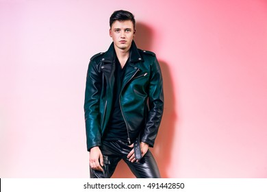 Handsome fashion man portrait, beautiful male model wear black leather jacket, pant and t-shirt posing near pink wall