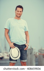 Handsome fashion man tourist on pier in port with yachts. Guy enjoying summer travel vacation by sea. Full length.