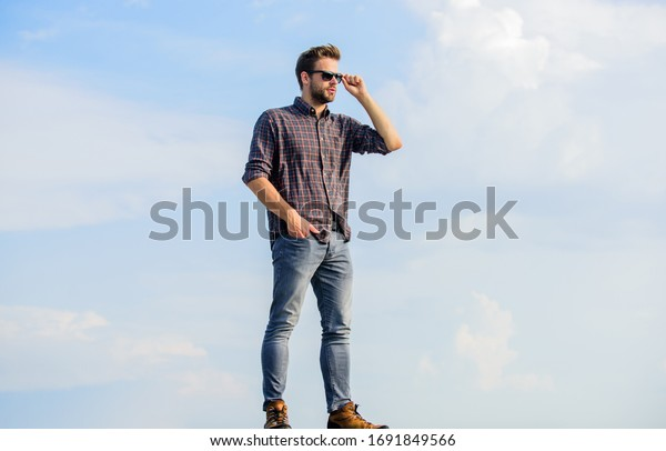 Handsome fashion model. businessman in glasses. confidence and charisma. macho man unshaven face. sexy man sky background. men beauty and sexuality. Real men. male fashion style. looking very trendy.