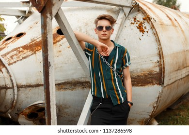 Handsome fashion model man with sunglasses in a fashionable beach shirt posing outdoors
