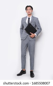 Handsome fashion young businessman in gray suit holding black handbag and looking at camera isolated on white background, full body