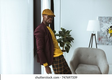 handsome fashionable african american man pising in checkered pants, cap and jacket in modern office