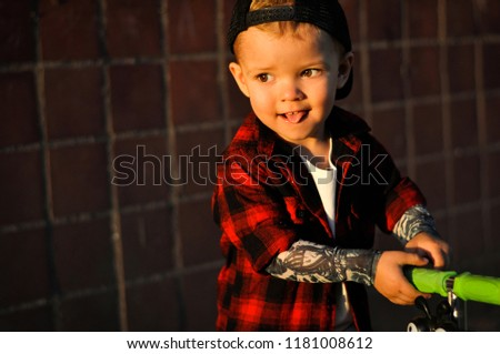 162ca86a6 A handsome fashionable baby boy in a T shirt with tattooed sleeves, a hip  hop