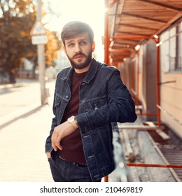 Handsome fashionable bearded man standing in the sunset on the street