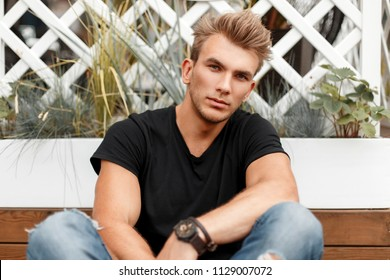 handsome fashionable guy with a hairstyle in a black T-shirt with jeans sitting near a white fence on the street