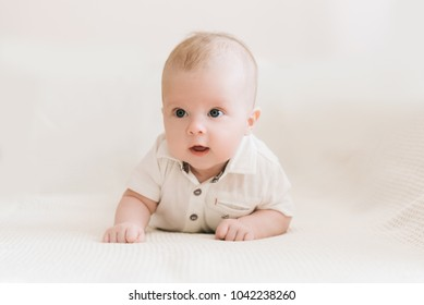 Handsome fashionable little boy lying on a blanket, with a sweet expression