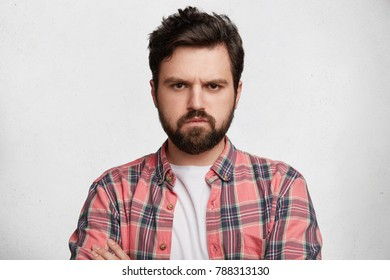 Handsome fashionable male has thick beard, dressed in checkered shirt, looks with grumpy expression at camera, being displeased after quarrel with girlfriend, isolated over white concrete wall
