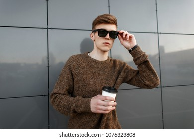 Handsome fashionable man with coffee corrects sunglasses on the street near the wall