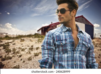Handsome fashionable man in sunglasses and a blue checked shirt posing outdoors with a wooden cabin behind and copyspace looking into the center of the frame