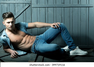 Handsome fashionable sexy sensual muscular young macho man with bare torso and stylish hair in jeans shirt indoor lying on wooden background, horizontal picture