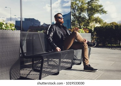 Handsome fashionable young man in a black leather jacket sitting on the bench on a sunny day